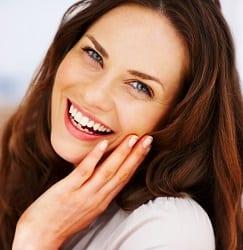 Smiling woman touching face