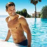 handsome smiling man in swimming pool in summer scenery-img-blog