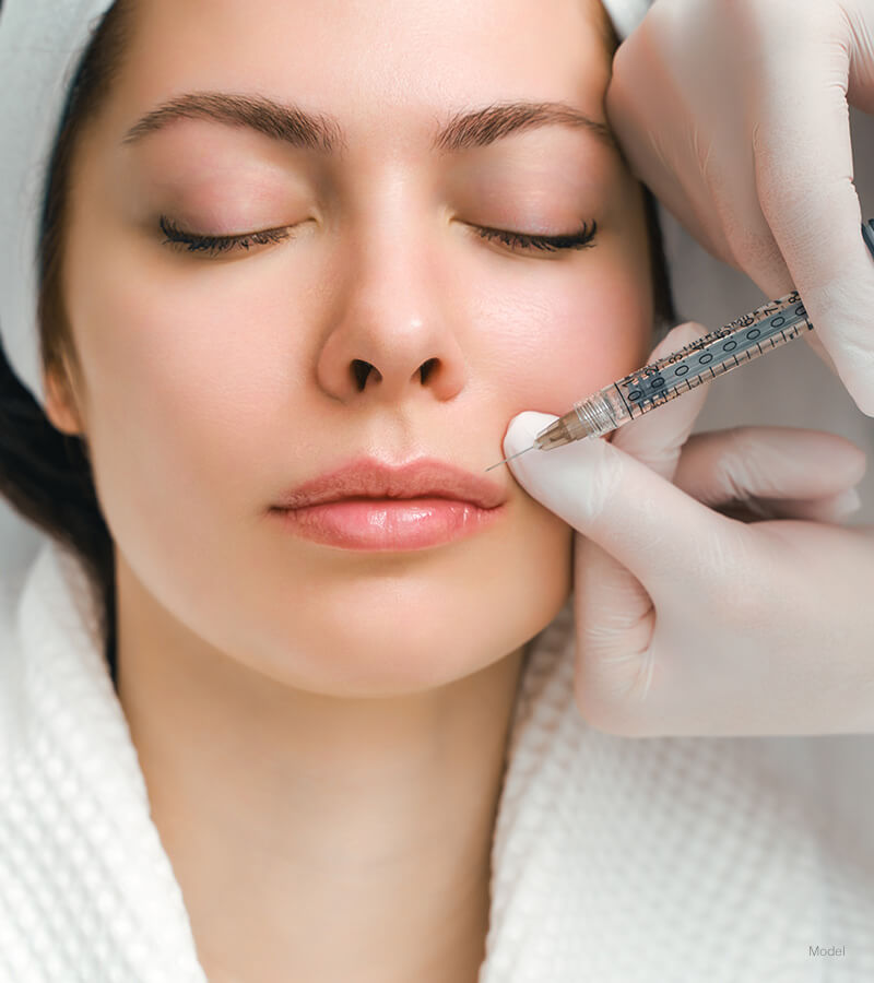 Woman with eyes closed getting facial injection